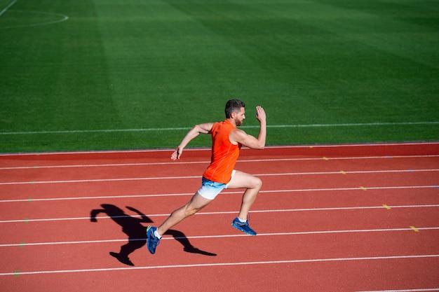 Uomo muscolare atletico in esecuzione su pista allo stadio all'aperto, finitura.