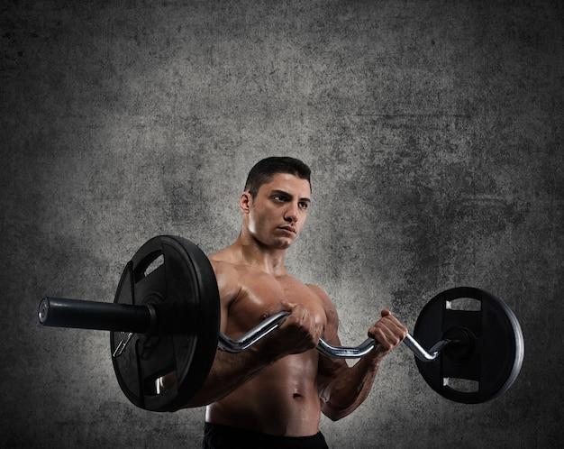 Uomo muscoloso atletico che allena i bicipiti in una palestra grunge