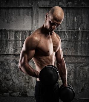 Uomo muscoloso atletico allenamento bicipite con manubri