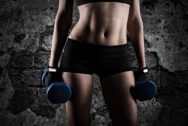 Bicipiti di formazione atletica donna muscolare con manubri sulla parete del grunge