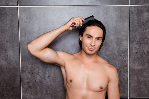 Uomo nudo atletico che pettina i capelli sullo spazio grigio