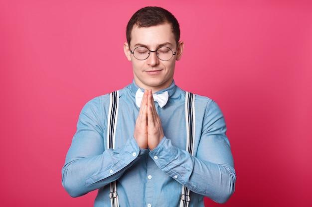 Atletico giovane pacifico in piedi con gli occhi chiusi, unisce i palmi delle mani, prega con un sorriso sul viso.