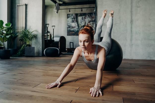 Signora atletica snella con i capelli rossi che esegue esercizi di stretching sulla parte superiore del grande fitball d'argento in un ambiente di sfondo dello studio fitness, concentrandosi sull'esercizio per forza ed equilibrio