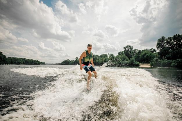 Surfista atletico che guida wakeboard per eseguire le sue abilità professionali