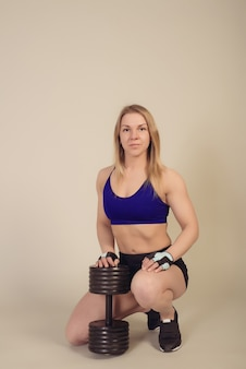 Il bodybuilder atletico della donna si siede con un manubrio pesante