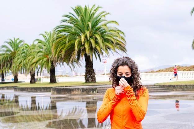 Donna atletica che copre la bocca e il naso con la maschera sulla strada