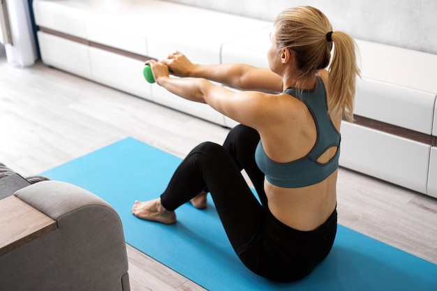 Donna atletica facendo esercizio di allenamento con manubri a casa