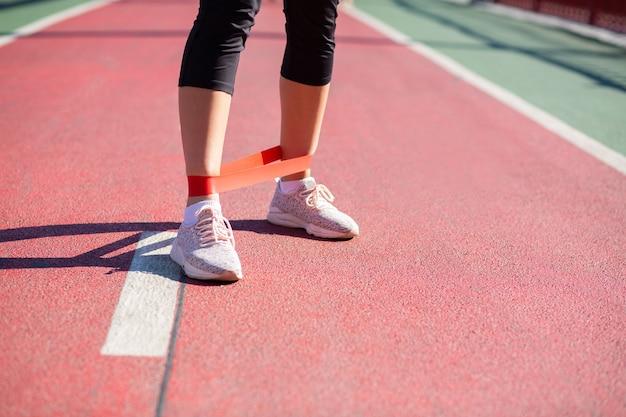 Donna atletica che si allena con banda di resistenza su un ponte. spazio per il testo