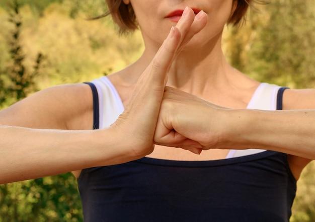 Donna atletica che fa le mani della donna all'aperto di yoga?
