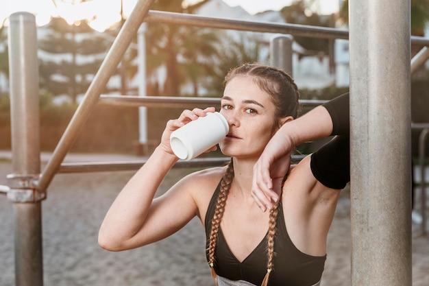 Donna atletica che beve soda dopo aver lavorato in spiaggia