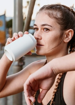 Donna atletica che beve soda in spiaggia dopo l'allenamento