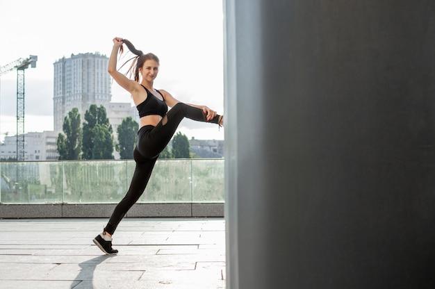 Donna atletica impegnata in atletica leggera, si allena al mattino per strada, una donna fa stretching e trucchi di ginnastica