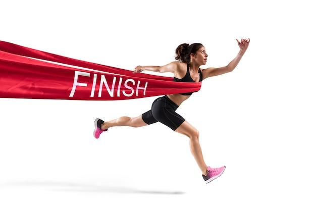 La donna atletica va oltre il nastro rosso all'arrivo di una gara