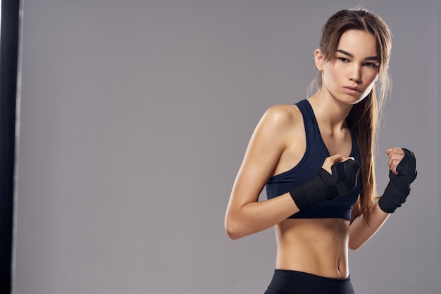 Fondo isolato combattente di allenamento del pugno delle bende della mano della donna atletica