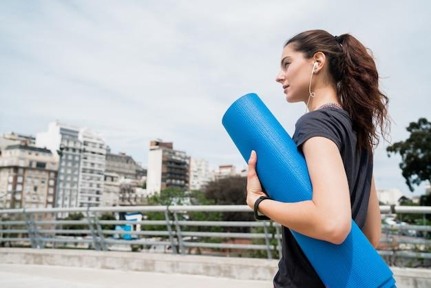 Donna atletica che tiene una stuoia di addestramento