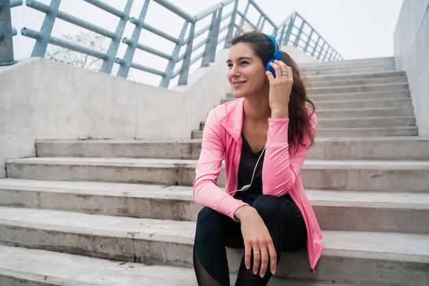 Donna atletica che ascolta la musica su una pausa dall'allenamento.