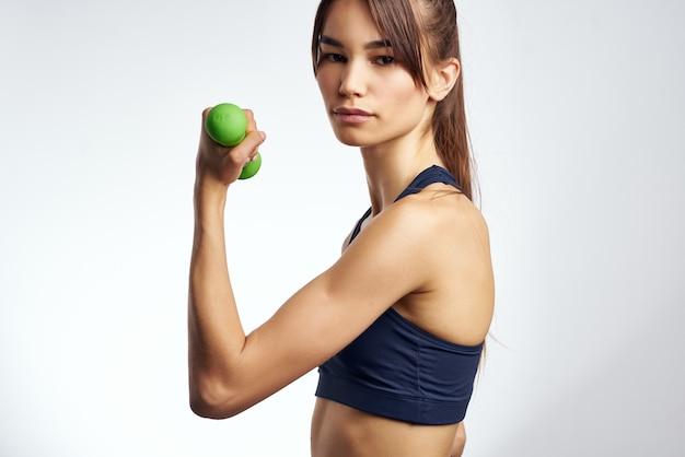 Donna atletica allenamento muscolare figura snella esercizio palestra sfondo chiaro