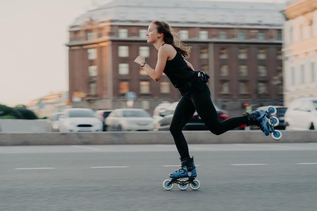 La donna atletica cavalca sui rulli si muove molto velocemente vestita con abbigliamento attivo si diverte a pattinare essere fotografata in pose d'azione in un luogo urbano impegnato in sport estremo. concetto di stile di vita attivo