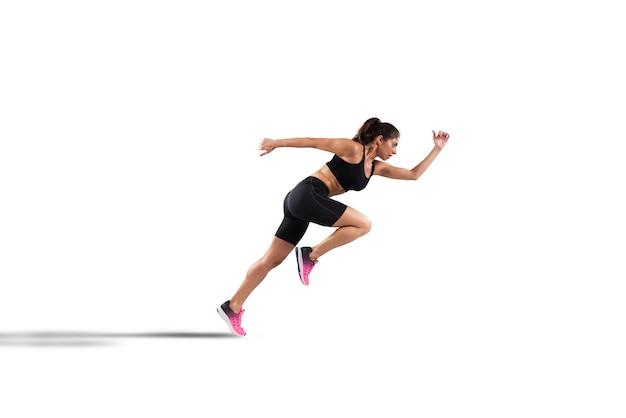 Corridore atletico della donna in abiti sportivi sull'asfalto di una strada isolata sulla parete bianca