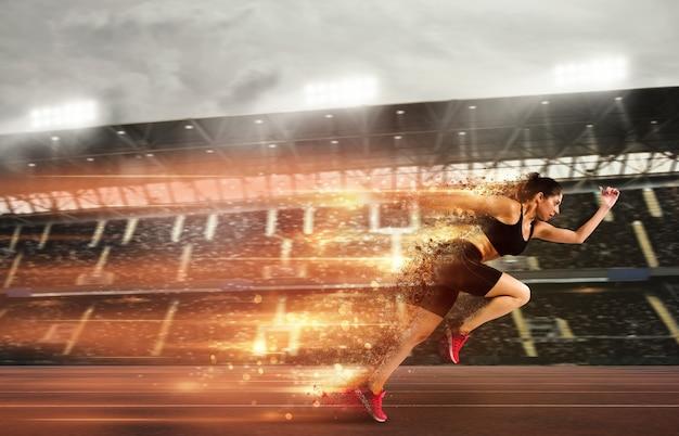 Donna atletica corre in una competizione sportiva con tracce di luci sulla pista dello stadio