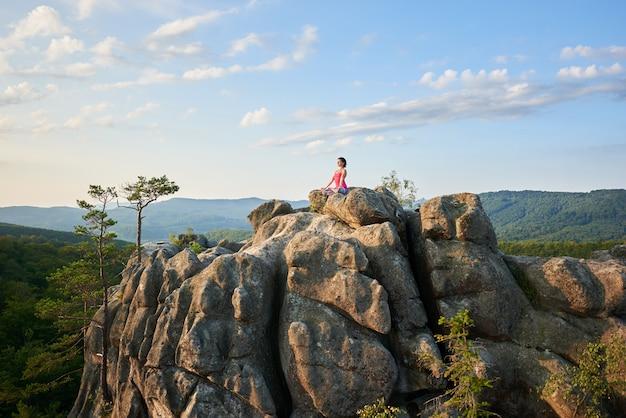 Donna atletica che si siede nella posa del loto sopra illuminata dalla cima del sole di estate di roccia enorme