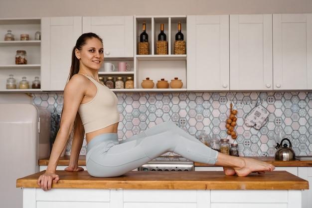 Donna atletica in abiti sportivi in posa sul piano del tavolo. il concetto di bellezza, salute, corretta alimentazione. donna sorridente e guardando la telecamera