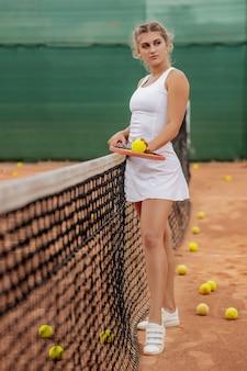 Donna atletica in piedi vicino a rete in campo con la racchetta in mano