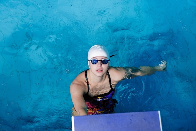 Donna atletica in cappello e occhiali da nuoto in piscina
