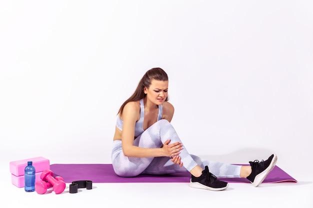 Donna atletica che tocca caviale ferito che soffre di affaticamento muscolare del polpaccio dopo l'allenamento yoga