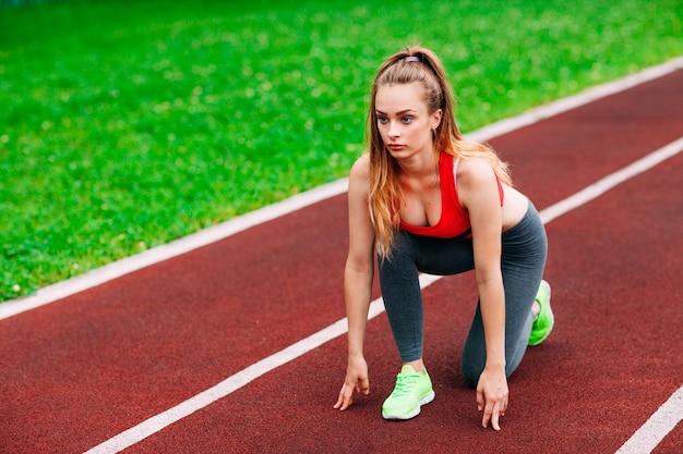 Donna atletica in pista iniziando a correre. concetto di fitness sano con uno stile di vita attivo.