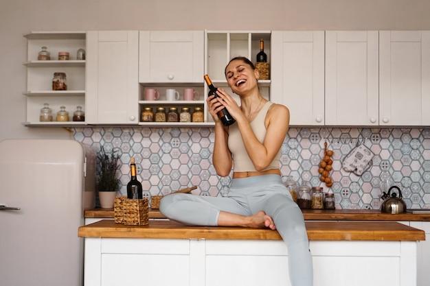 Donna atletica in tuta in una cucina leggera beve vino rosso da una bottiglia dopo aver fatto sport. la donna ride