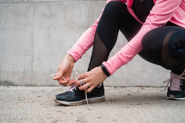 Donna atletica che lega i suoi laccetti. Foto Premium