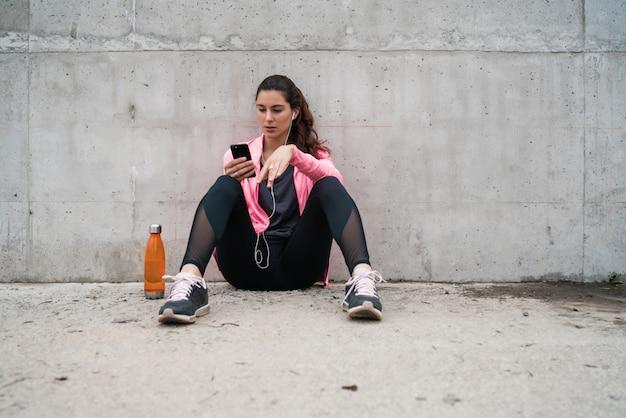 Donna atletica che per mezzo del suo telefono.