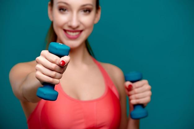 Donna atletica che indossa abiti da fitness che si esercita con il fuoco selettivo indoor con manubri