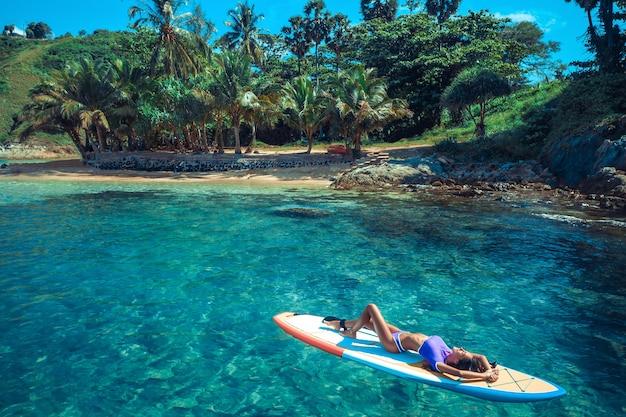 Donna atletica con un bel corpo in posa mentre giaceva in bikini su una tavola da surf