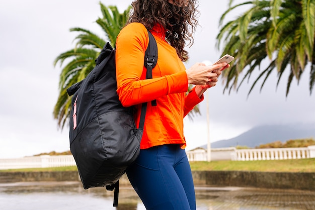 Donna atletica con borsa sportiva e smart phone sulla strada