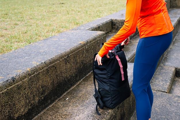 Donna atletica con borsa sportiva sulla strada