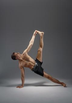 Yoga atletico facendo esercizio di stretching in studio, muro grigio uomo forte che pratica yogi, allenamento asana, massima concentrazione, stile di vita sano