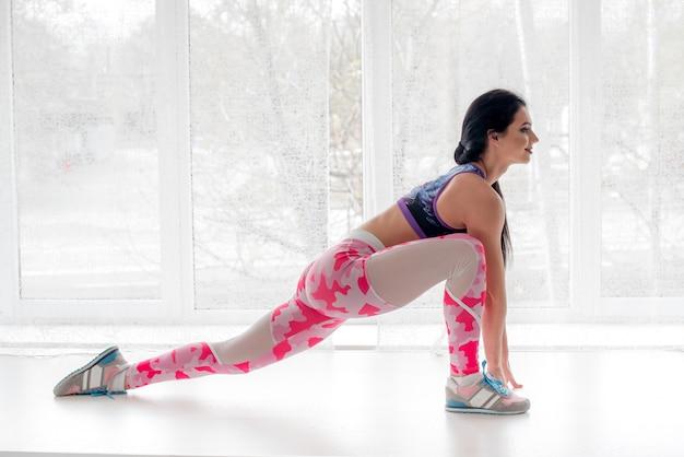 La ragazza atletica si esercita nello studio su un fondo leggero. fitness, stile di vita sano