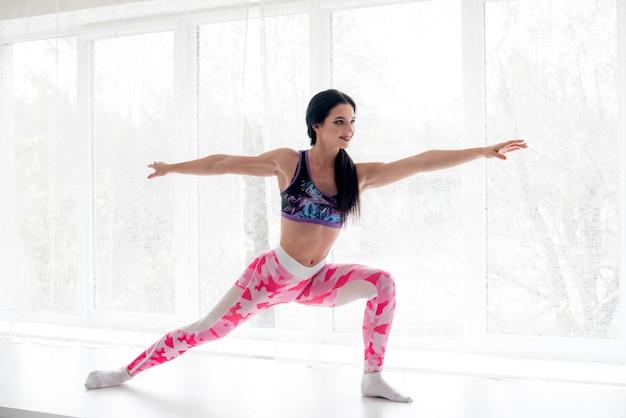 La ragazza atletica esegue il riscaldamento su una stanza leggera. fitness, stile di vita sano