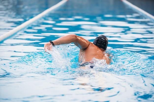 Giovane atletico che nuota la schiena strisciare in una piscina.