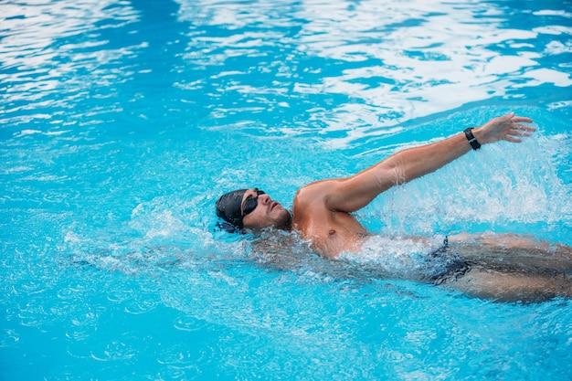 Giovane atletico che nuota sullo stile di dorso. gara di nuoto.