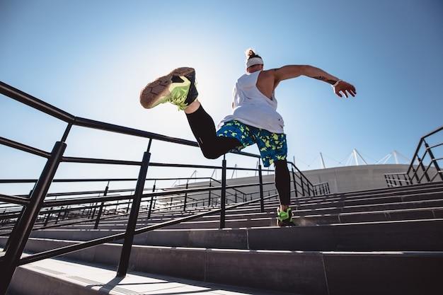 Giovane atletico con fascia in testa vestito con maglietta bianca, leggings neri e pantaloncini blu sta saltando su per le scale fuori in una giornata di sole.