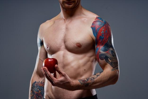Giovane atletico con muscoli muscolosi e salute della mela torso nudo abs