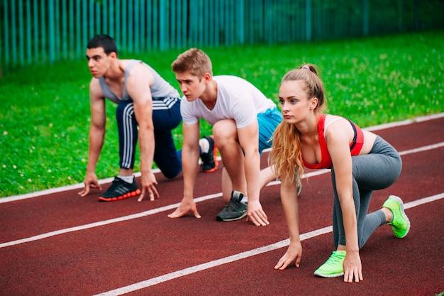 Giovani atletici in pista che iniziano a correre. concetto di fitness sano con uno stile di vita attivo.