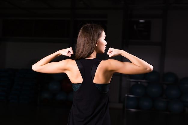 Giovane donna atletica che mostra i muscoli della schiena e delle mani su uno sfondo nero isolato.