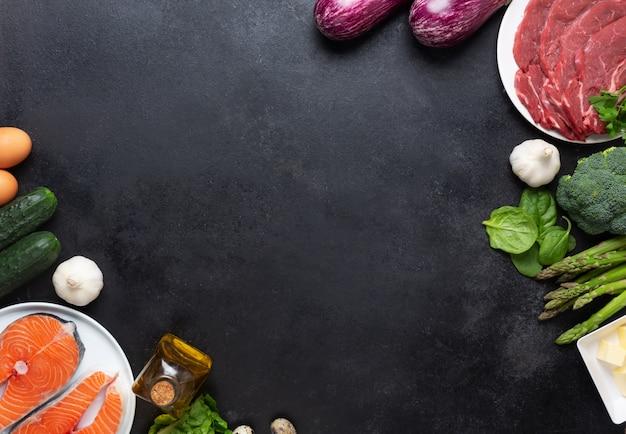 Ingredienti alimentari di dieta di atkins sulla lavagna posteriore, concetto di salute, vista superiore con lo spazio della copia