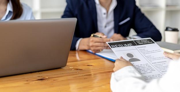 L'atmosfera della stanza dei colloqui nella start-up, il richiedente sta consegnando il curriculum all'intervistatore come documento di supporto per l'intervista, due intervistatori. concetto di colloquio di lavoro