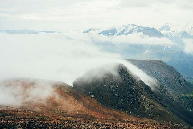 Atmosferico paesaggio alpino a gigantesche nuvole basse sopra montagne rocciose.