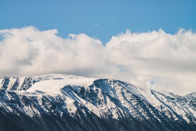 Atmosferico paesaggio alpino al crinale innevato nella giornata di sole.